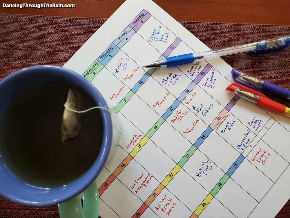 A cup of tea sitting on top of a December 2020 calendar filled out with all of the activities of the month next to three colored pens