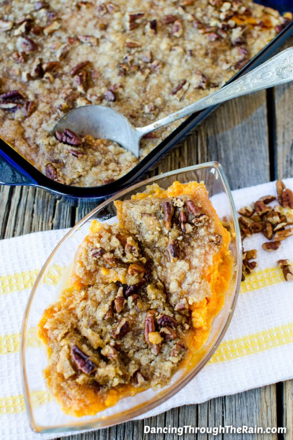 The Best Sweet Potato Casserole in a clear serving dish in front of a blue casserole dish with the rest of the casserole