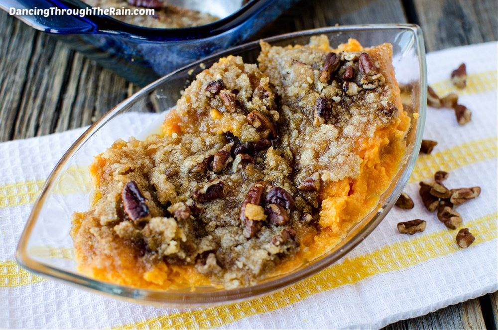 Sweet Potato Casserole with pecans in a clear casserole dish on a white and yellow fabric napkin on a wooden table