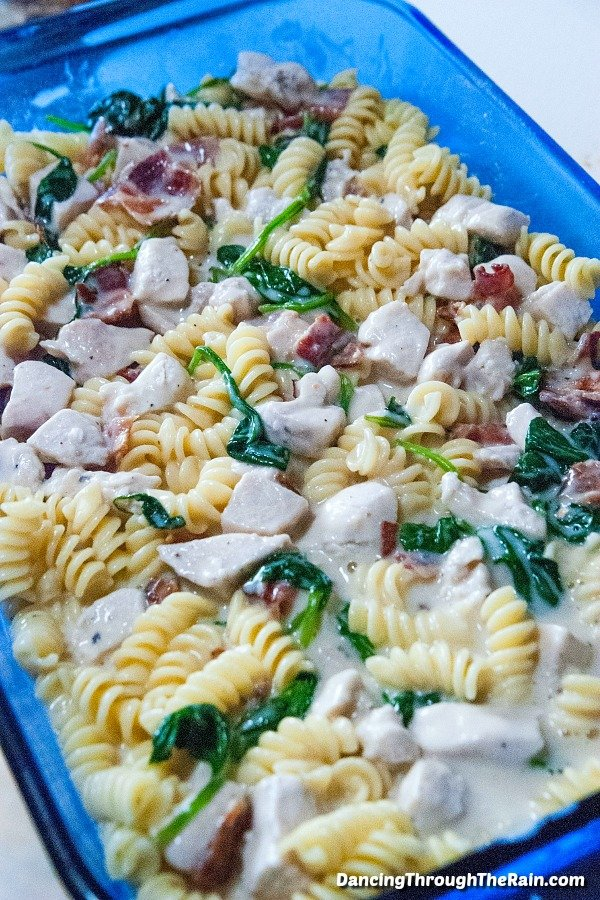 The Chicken Bacon Alfredo Pasta Bake in a clear blue baking dish