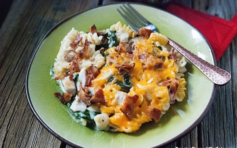 A green plate with a large scoop of Chicken Bacon Alfredo Pasta Bake next to a fork and a red napkin on a wooden table