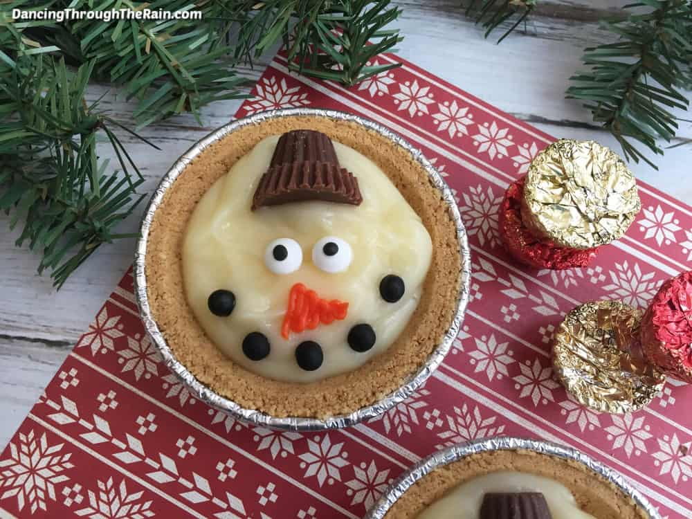 A Mini pudding pie on a red winter themed placemat next to gold and red reese's mini peanut butter cups