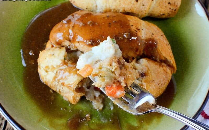 Two Chicken Pot Pie Crescent Roll Buns in a green dish with a fork holding mashed potatoes, carrots and chicken in front