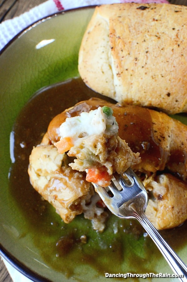 Two Chicken Pot Pie Crescent Roll Buns on a green dish with a fork full of mashed potatoes, peas and carrots