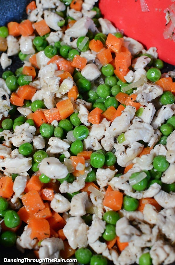Peas, carrots and chicken being cooked in a pan