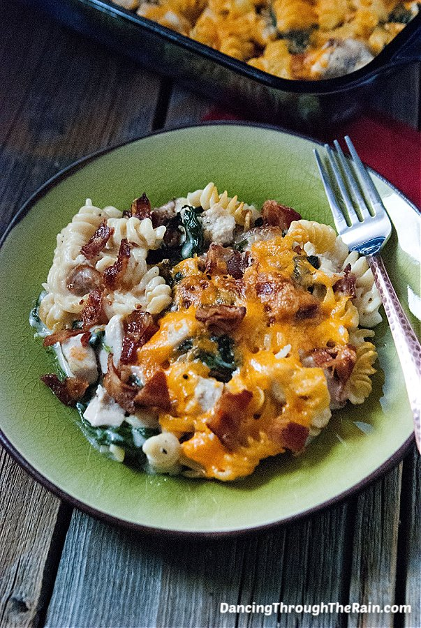 A scoop of Chicken Bacon Alfredo Pasta Bake on a green plate with a metal fork on a wooden table next to the rest of the casserole in the baking dish