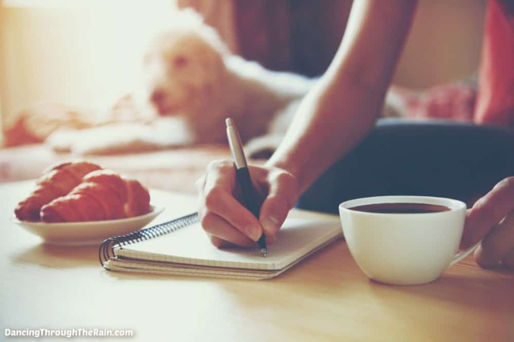 A woman writing in a journal with a pen while holding a white mug of coffee and a white dog is looking on in the background