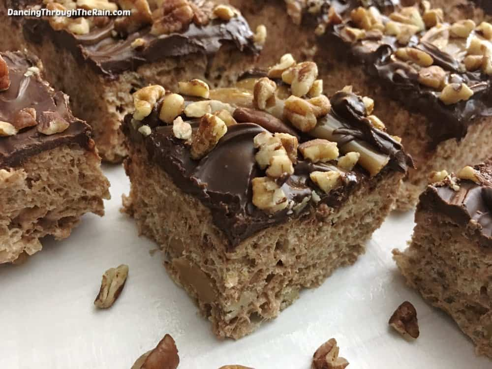 Five Turtle Krispie Treats on a white table with pecans scattered around them
