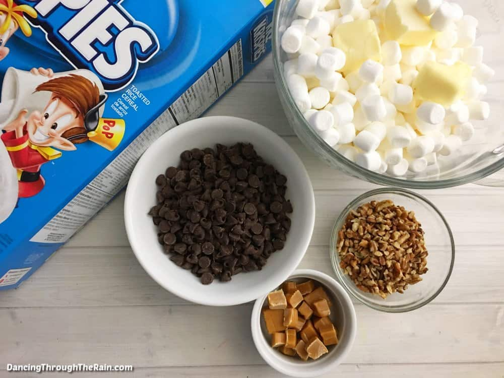 Ingredients for Turtle Rice Krispie Treats: A blue box of Rice Krispies next to a white bowl of chocolate chips, a white bowl of caramel squares, a clear bowl of pecans and a clear bowl of mini marshmallows