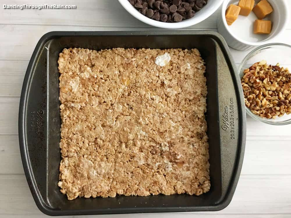 Turtle Rice Krispie Treats flattened in a metal baking pan next to a white bowl of chocolate chips. a white bowl of four caramel squares and a clear bowl of pecans