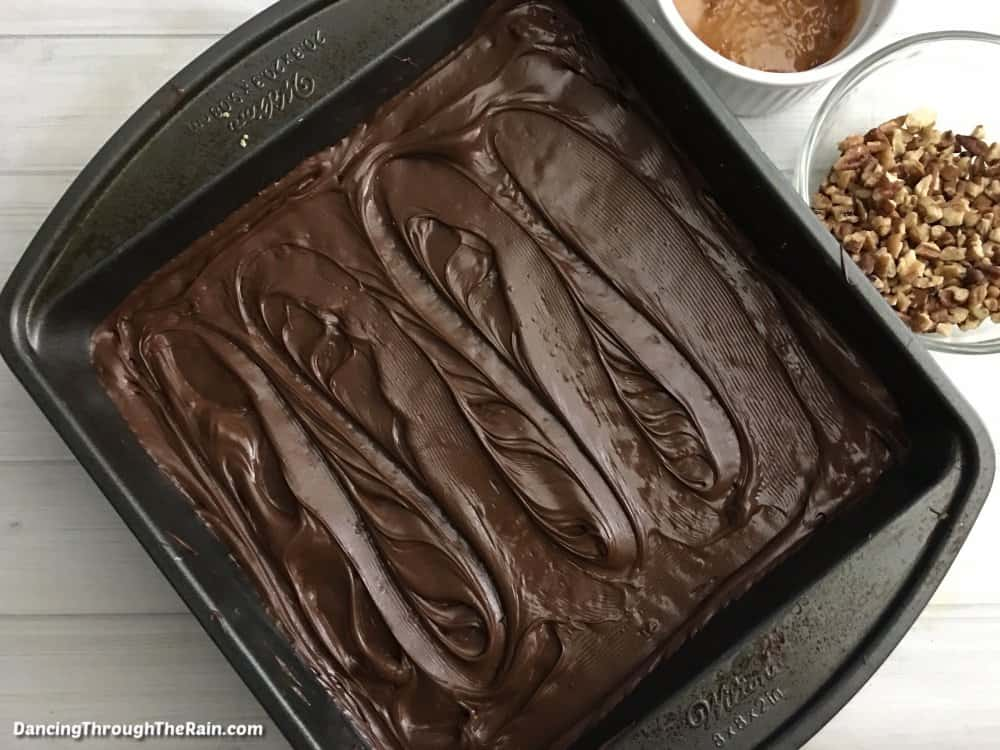 A metal baking pan with a chocolate layer on top of hidden Turtle Krispie Treats next to a clear bowl of pecans