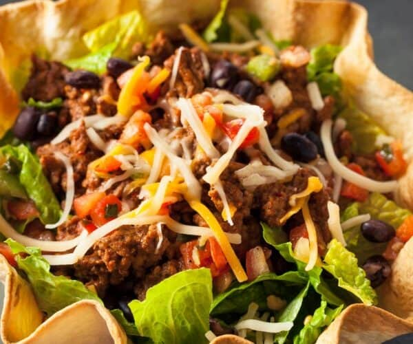 A Taco Salad in a taco shell with the words What To Serve With A Taco Salad