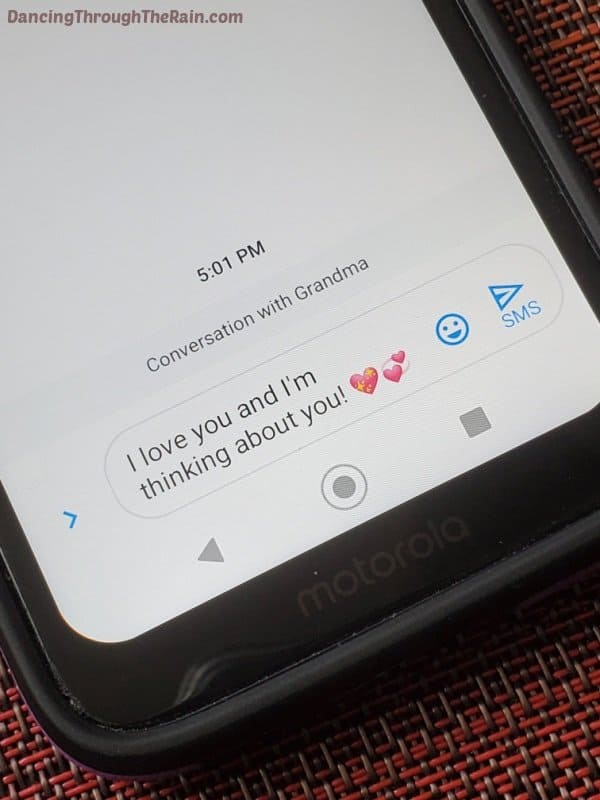 A cell phone with a text to grandma that says I love you and I'm thinking about you