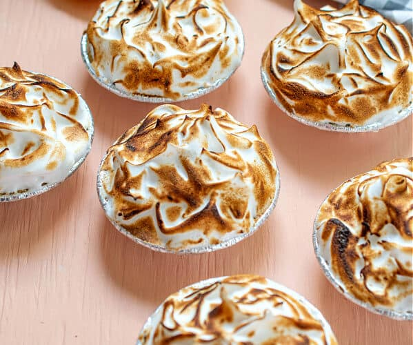Six No-Bake Mini Lemon Meringue Pies on a salmon colored table with lemons and a blue and white checkered napkin