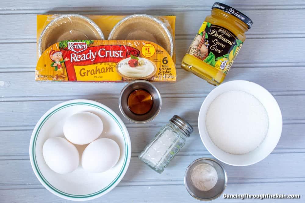 Ingredients for the No-Bake Mini Lemon Meringue Pies including lemon curd, mini graham cracker crusts, eggs, vanilla extract and more