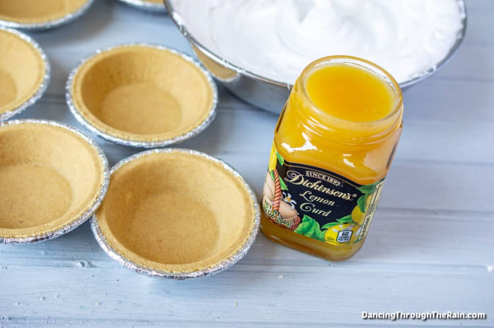 Five mini graham cracker crusts in tins next to a bowl of meringue and a jar of Dickinson's lemon curd