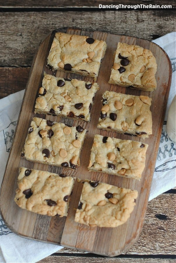Eight Peanut Butter Chocolate Chip Cookie Bars cut on a wooden cutting board on a white tablecloth on a wooden table