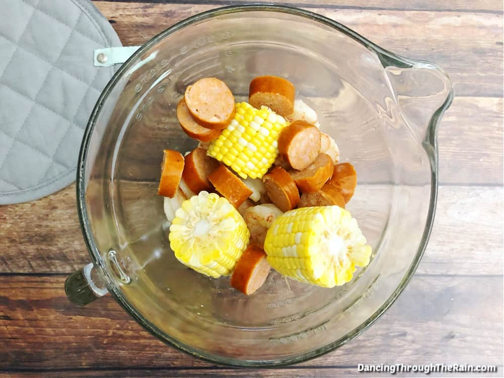 A clear mixing bowl with pieces of andouille sausage and corn on the cob visible inside on a wooden table