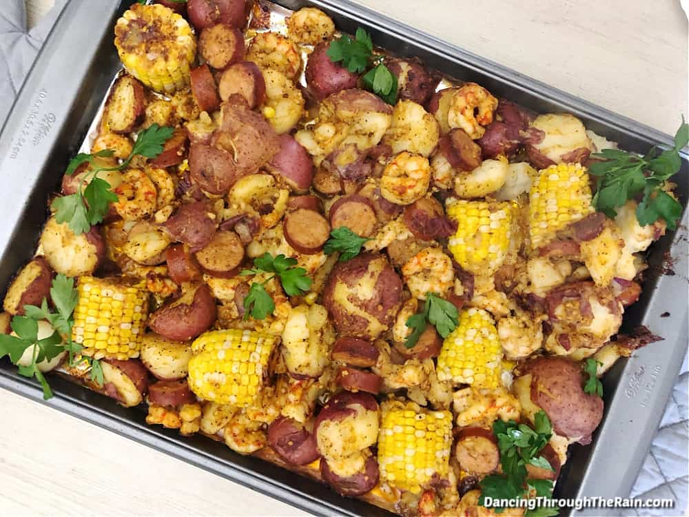 A sheet pan shrimp boil with visible corn on the cob, potatoes, shrimp, andouille sausage and parsley on a wooden table