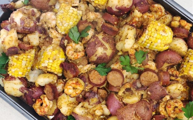A closeup of the Sheet Pan Shrimp Boil with corn, potatoes, andouille sausage and shrimp visible
