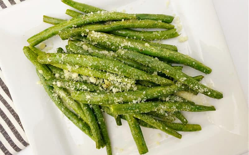 A pile of grilled green beans on a white square plate