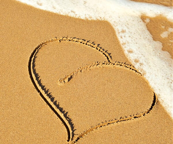 A heart drawn in the sand with a wave coming to erase it with the words How To Truly Forgive Yourself