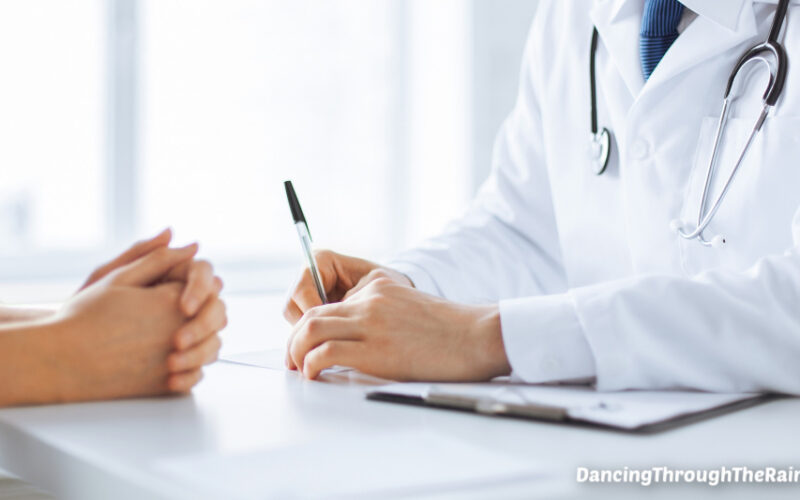 A doctor and patient talking with their hands on a white table