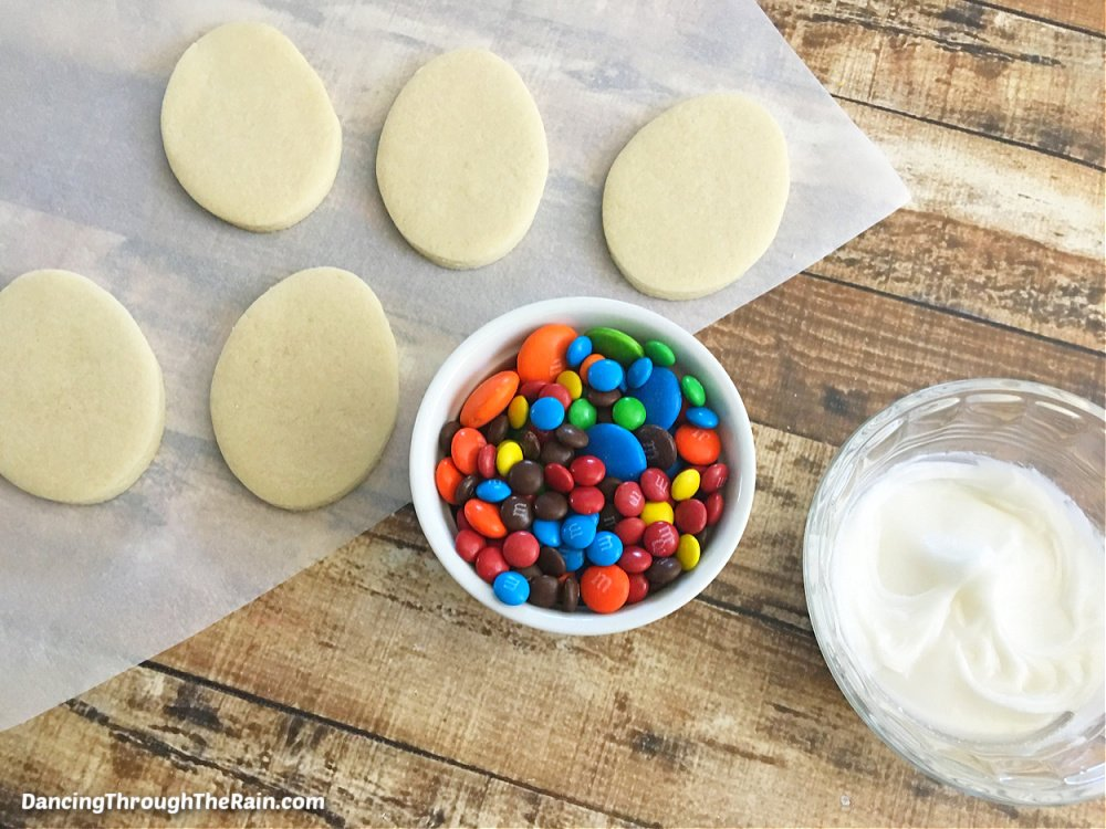 """Five egg shaped cookie dough pieces on parchment paper next to a white bowl of M&M""""s and a clear white bowl of white icing"""
