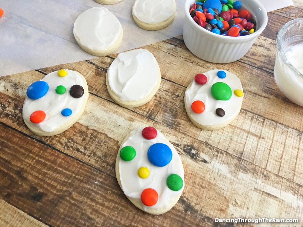 Dinosaur Egg Cookies being decorated with different sizes and colors of M&M's