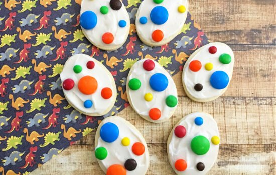 Seven decorated Dinosaur Egg Cookies on a wooden table with