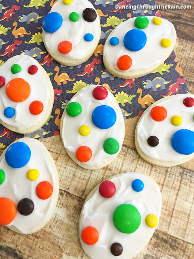 Seven decorated Dinosaur Egg Cookies on a wooden table