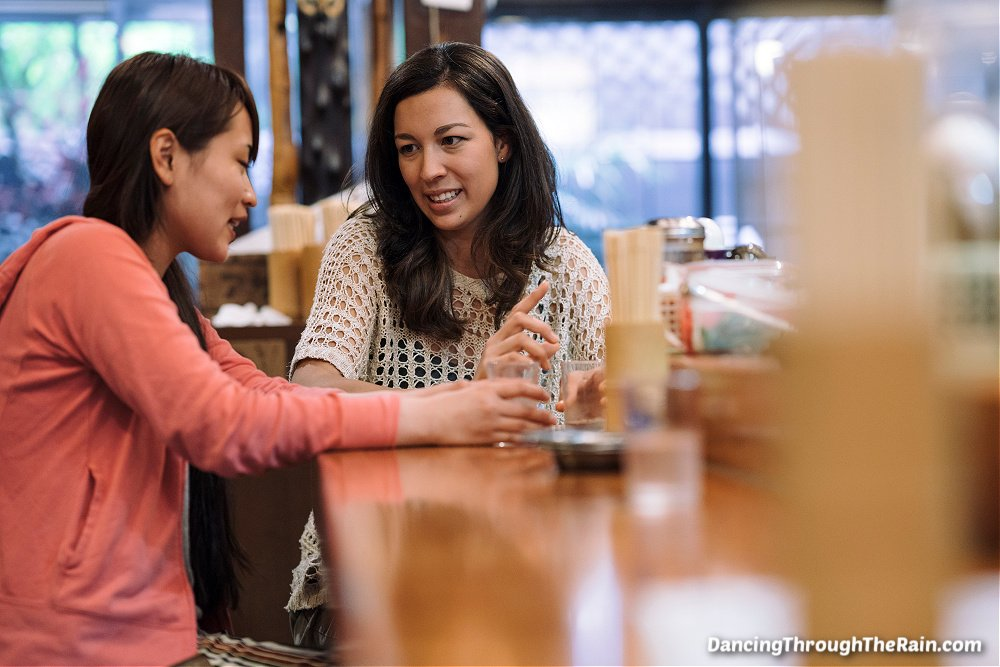 Two women talking at a bar with drinks