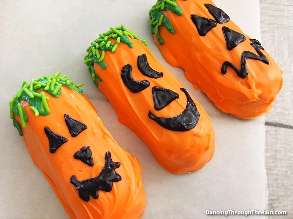 Three Halloween Jack O Lantern Twinkies on a piece of parchment paper
