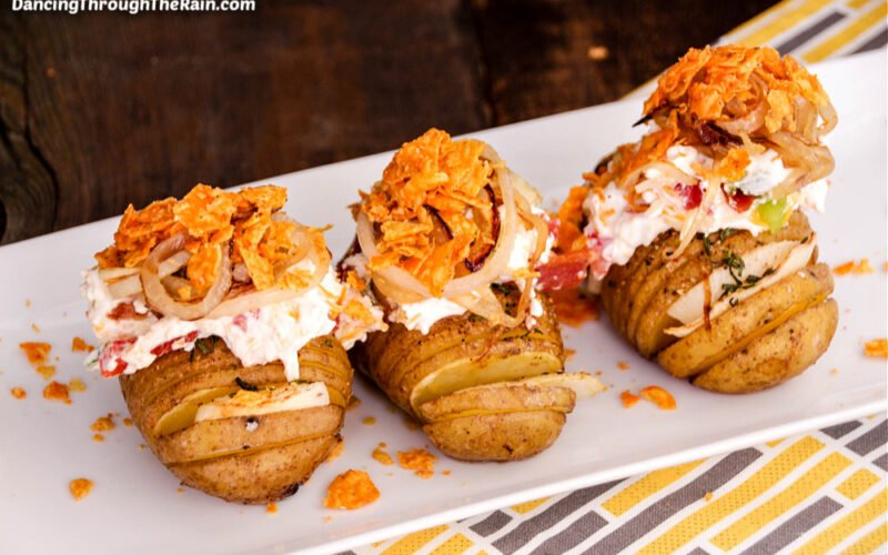 Three Loaded Hasselback Potatoes on a white rectangular plate with Dorito chips laying next to them