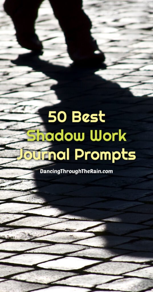 A person standing on a cobblestone street with a visible shadow and the words 50 best shadow work journal prompts