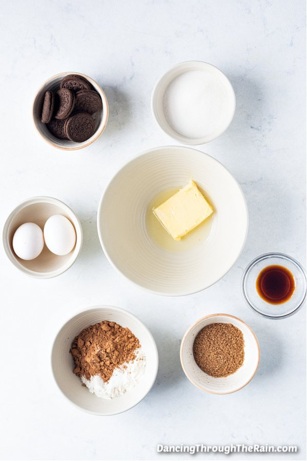 A white table with white bowls of butter, Oreo cookies, granulated sugar, cocoa powder, vanilla extract and two eggs