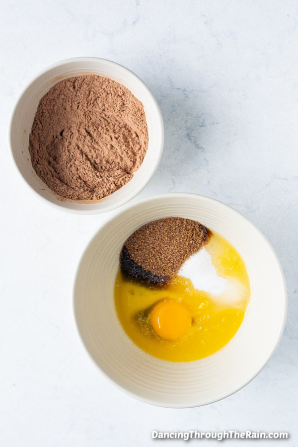 One white bowl of eggs, vanilla, brown sugar, melted butter, and granulated sugar in a white bowl next to a bowl of flour and cocoa powder