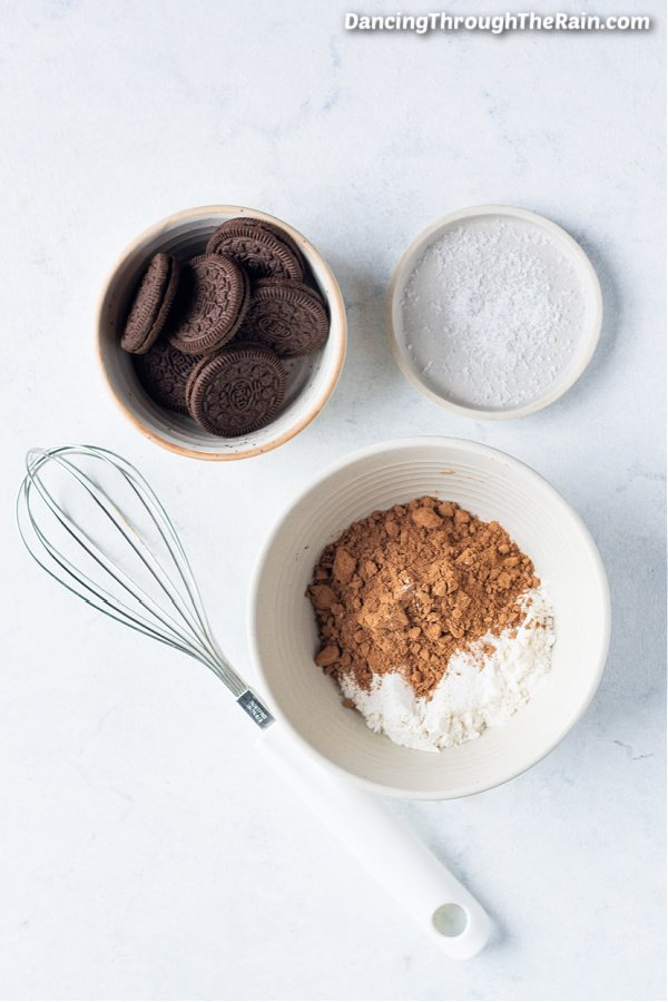 A white bowl of granulated sugar, another of flour, and another of Oreo cookies next to a metal whisk