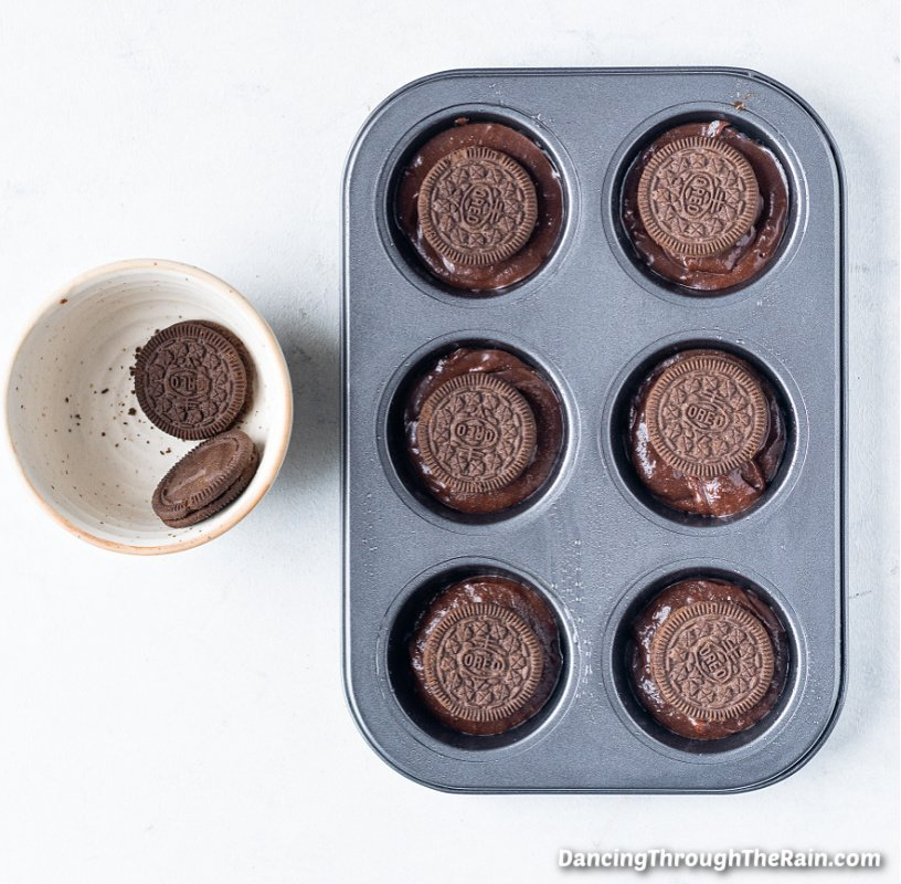 A muffin tin with brownie batter and a whole Oreo cookie in each muffin cup next to a white bowl of two Oreo cookies on a white plate