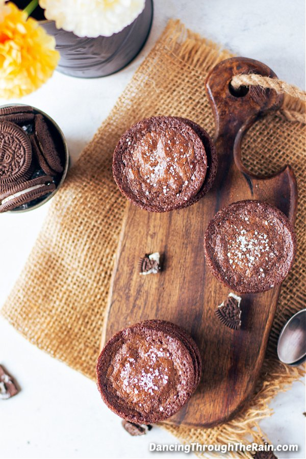 Three Oreo Stuffed Brownies on a wooden cutting board on a piece of brown burlap next to a yellow flower and a tin bowl of Oreo cookies