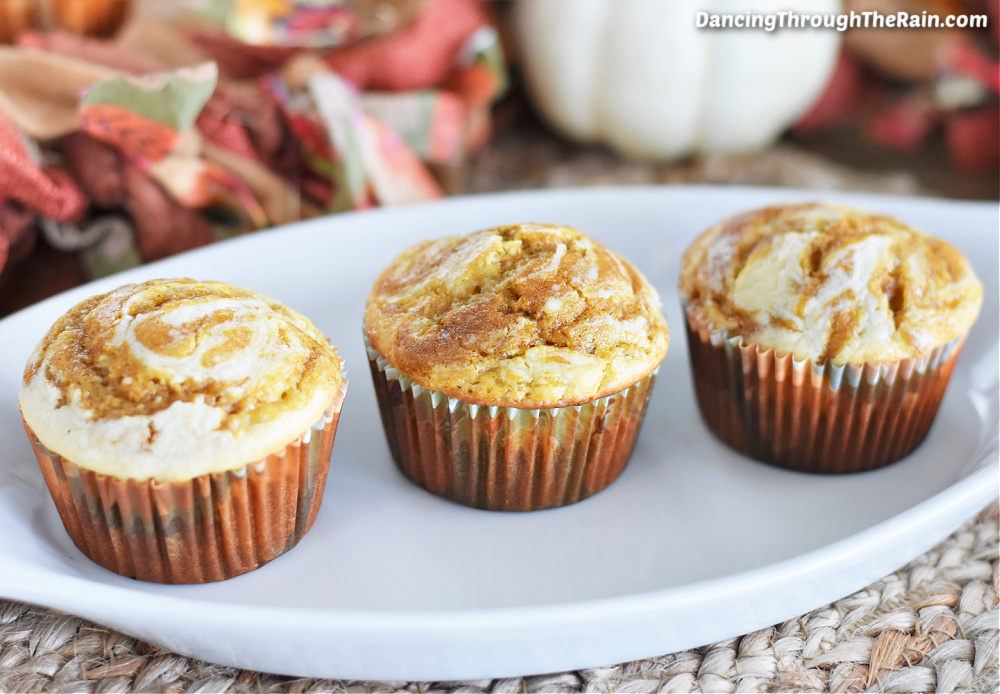 Three Pumpkin Cheesecake Muffins on a white serving plate with a white pumpkin and fall colored fabric in the background