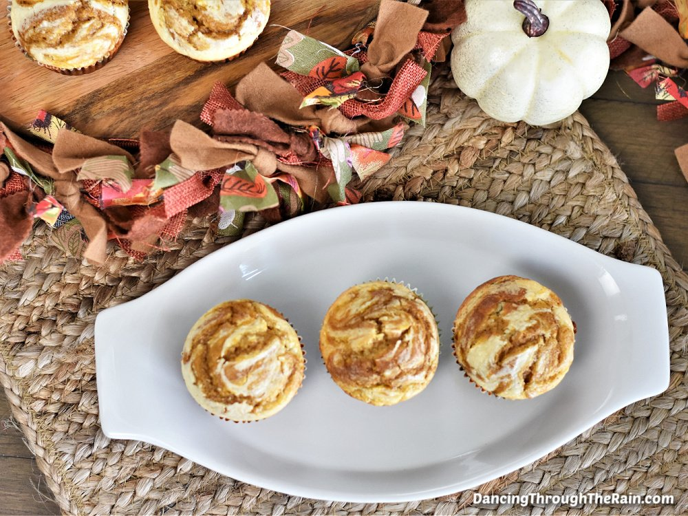 Three Pumpkin Cheesecake Muffins on a white plate next to a piece of fall-colored fabric, a white pumpkin, and a cutting board with more muffins on top