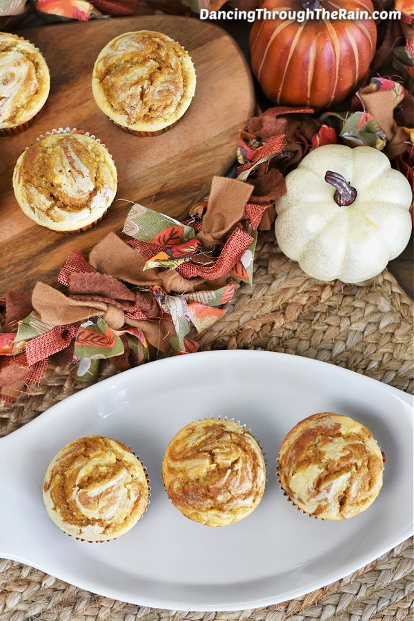 A white tray of three Pumpkin Cheesecake Muffins next to a wooden cutting board of three more and a white and orange pumpkin in the middle