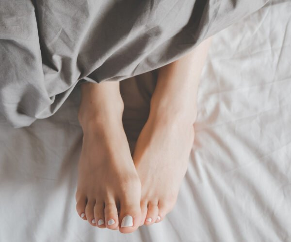A woman with white painted nails with only her two feet showing in a bed with gray sheets with the words 21 Ways To Comfort Yourself No Matter What Is Wrong