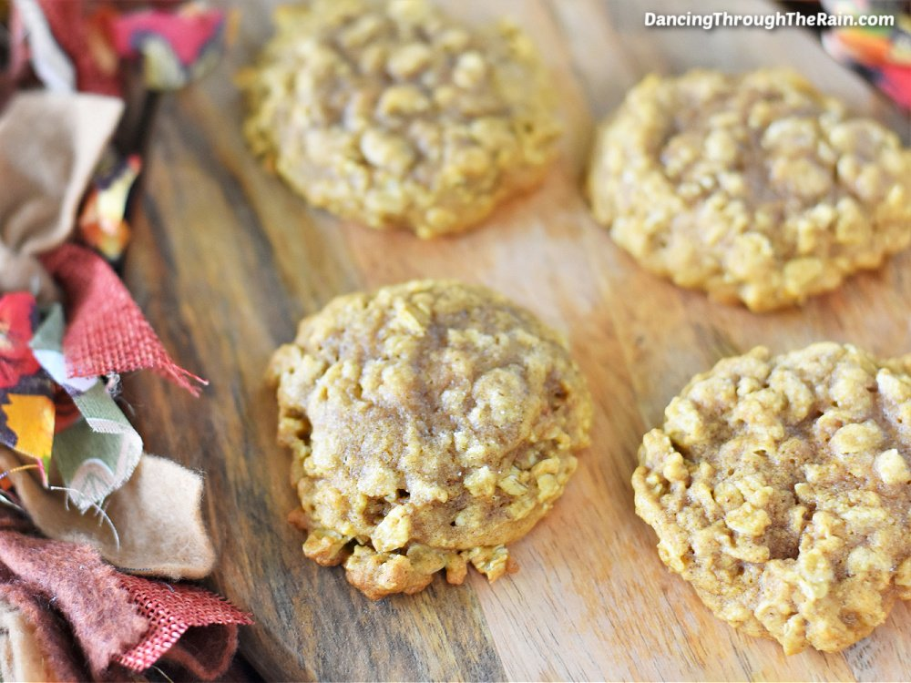 Four Pumpkin Oatmeal Cookies on a wooden cutting board next to fall colored fabrics