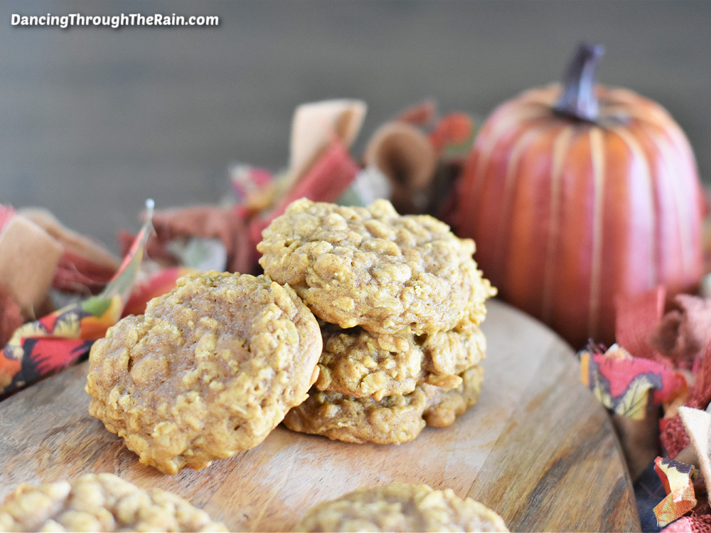 Six Pumpkin Oatmeal Cookies on a wooden cutting board in front of an orange pumpkin and fabric with fall colors