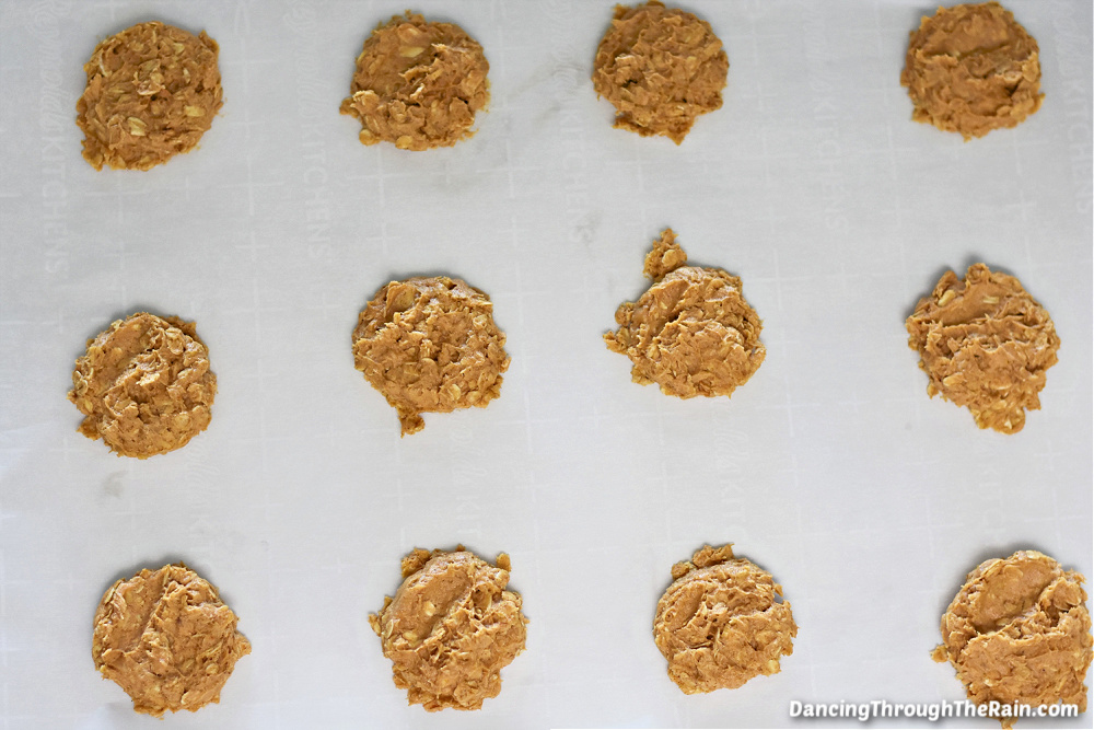 A parchment paper lined cookie sheet with Pumpkin Oatmeal Cookie batter in scoops on the sheet