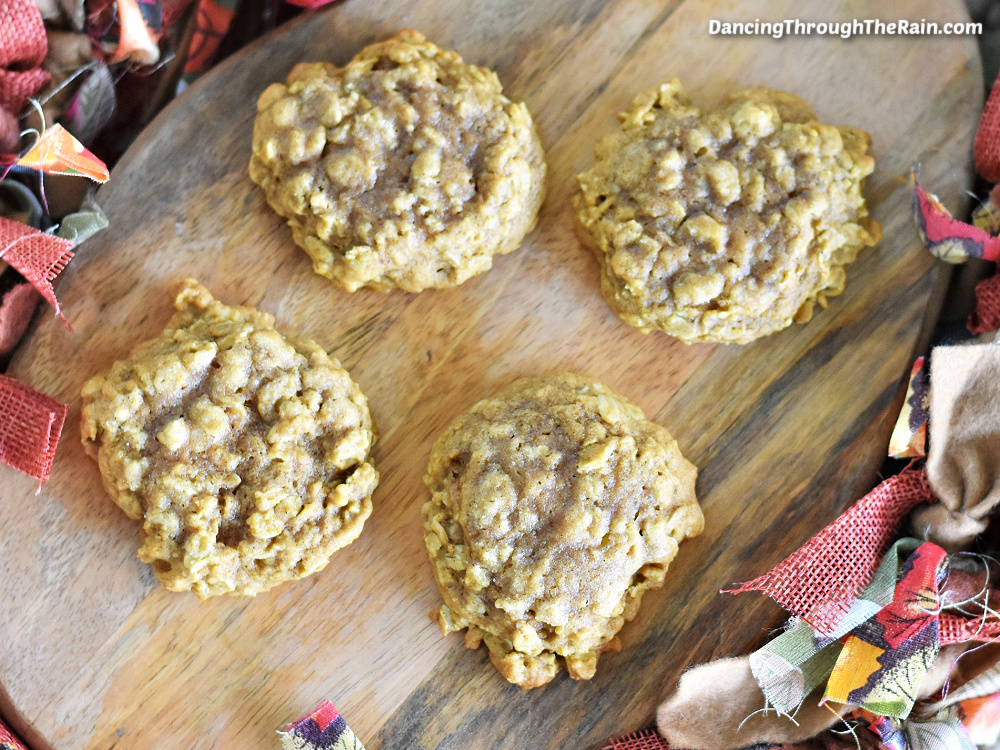 Four Pumpkin Oatmeal Cookies on a wooden cutting board next to fabric with fall colors